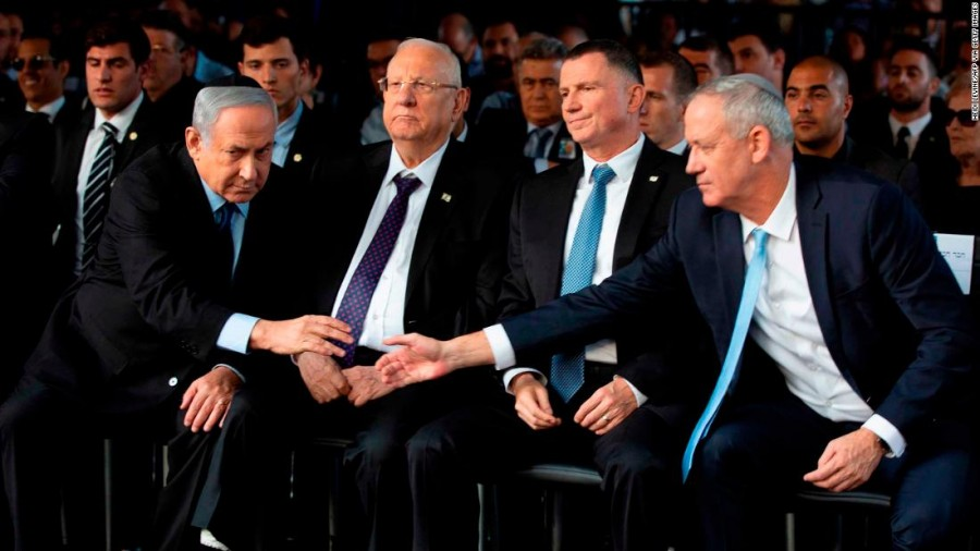 Israeli Blue and White party chief Benny Gantz (R), shakes hands with Prime Minister Benjamin Netanyahu (L) as they attend a state memorial ceremony for former Israeli prime minister Yitzhak Rabin (backround) and his wife Leah, at Mount Herzl in Jerusalem on November 10, 2019. (Photo by HEIDI LEVINE / POOL / AFP) (Photo by HEIDI LEVINE/POOL/AFP via Getty Images)